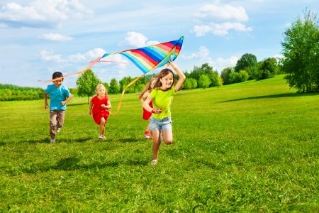 field stripped: Four little kids running in the park with kite happy and smiling