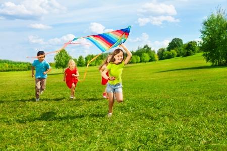 Vier kleine kinderen lopen in het park met vlieger blij en lachend