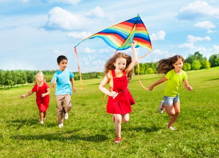 children playing outside: Group of four kids running in the park with kite happy and smiling on summer sunny day Stock Photo