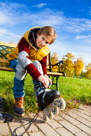 10 years old: Close portrait of 10 years old boy in casual autumn clothes putting on roller skates sitting on the bench in the park Stock Photo