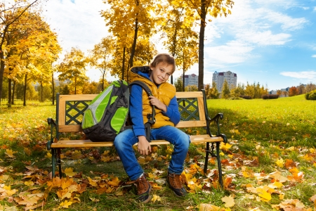 10 month: Happy 10 years old boy sitting on the bench with backpack after school with backpack on the shoulder