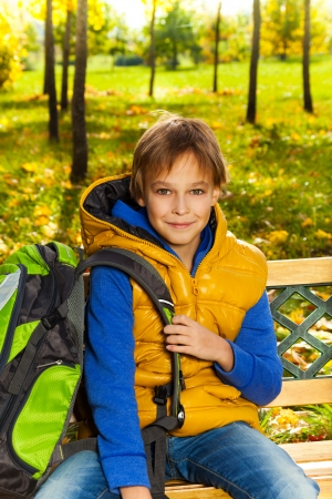 10 years old: Portrait of happy 10 years old boy sitting on the bench with rucksack with backpack after school