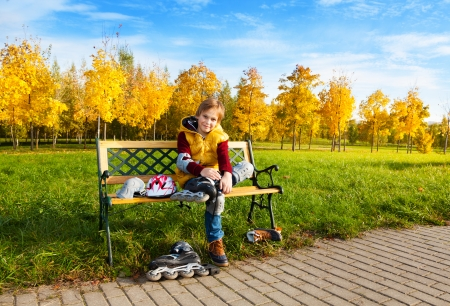 sitting on a bench: Nice boy in casual autumn clothes putting on roller skates sitting on the bench in the park
