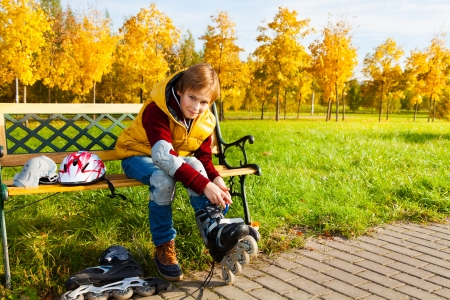 10 years old: Nice 10 years old boy in casual autumn clothes putting on roller skates sitting on the bench in the park
