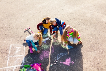 Group of four boys and girls, friends in autumn clothes painting with chalk on the asphalt photo