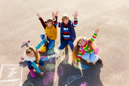 jugar: Grupo de cuatro niños y niñas, amigos en la ropa de otoño que pintan con tiza en el asfalto levantando las manos con sonrisa en los rostros de los suyos