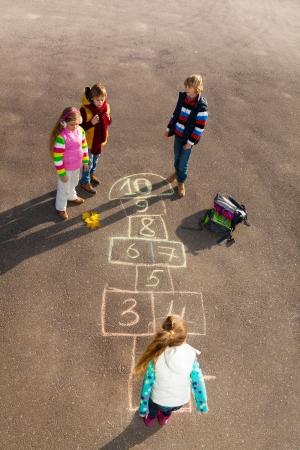 秋の服を着て学校後、アスファルトの上に描画石けり遊びゲーム ジャンプ子供たちのグループ