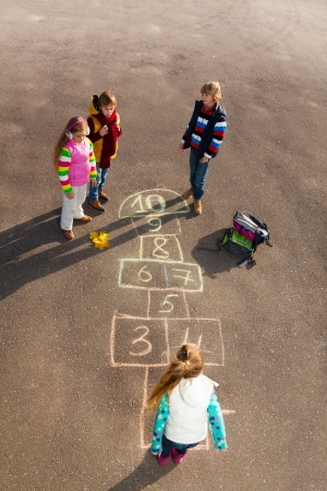 Group of kids jumping on the Hopscotch game drawn on the asphalt after school wearing autumn clothes photo