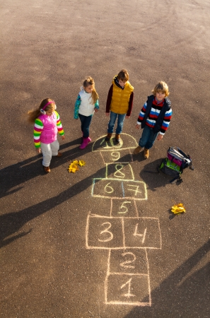 Group of kids jumping on the Hopscotch game drawn on the asphalt after school wearing autumn clothes after school