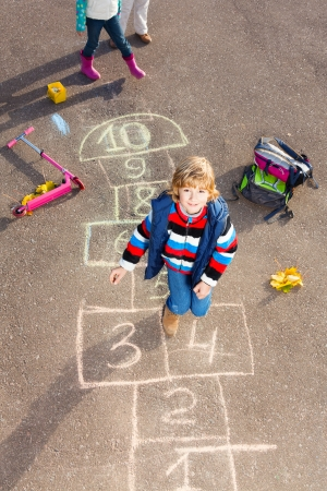 Boy jumping on the hopscotch game drawn on the asphalt looking up photo