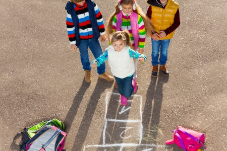 Group of three kids playing hopscotch game with girl jumping photo