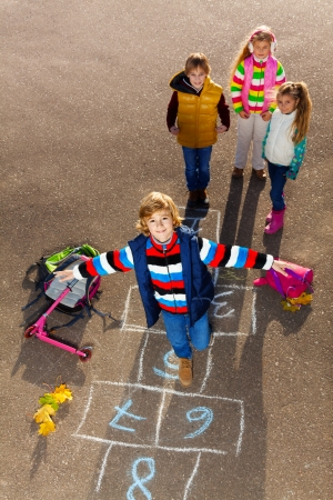 Boy jumping on hopscotch game with friends boys an girls standing by with school bags laying near photo