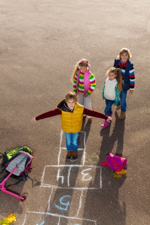 school friends: Boy jumping on hopscotch game with friends boys an girls wearing autumn clothes standing by with school bags laying near Stock Photo
