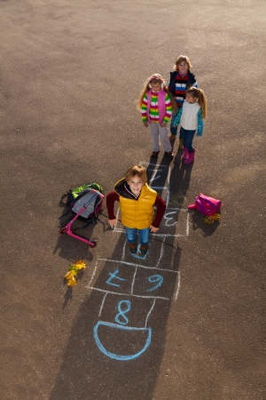 Boy jumping on hopscotch game with mates boys an girls standing by with school bags laying near photo