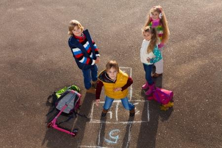 Gelukkige jongen springen op Hinkelspel spel met vrienden jongens een meisjes staan door met schooltassen tot in de buurt