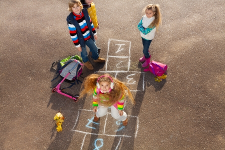 Happy girl jumping on hopscotch game with friends boys an girls standing by with school bags laying near photo