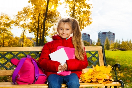 Nice girl sitting on bench in autumn park with backpack photo
