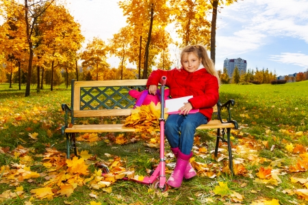 Little blond girl with long hair, backpack, papers sitting on the bench on autumn  photo