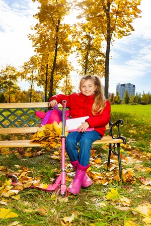 Little happy blond girl with long hair, backpack, papers sitting on the bench in the park on autumn  photo