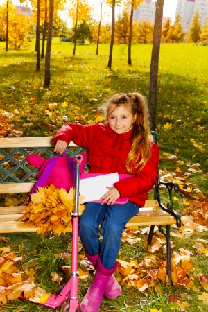 Little happy blond girl with long hair, backpack, papers sitting on the bench in the park on autumn sunny day photo