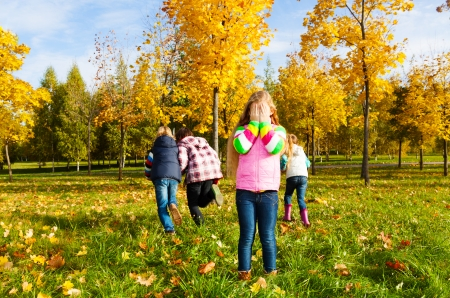 Kids play hide and seek with girl counting and friends running away Stock Photo