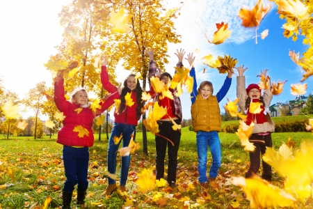 fall fun: Group of five kids, boys and girls throwing autumn maple leaves in the park on sunny day