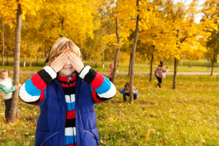 Kids play hide and seek with boy counting covering face with palms while others hiding behind trees photo