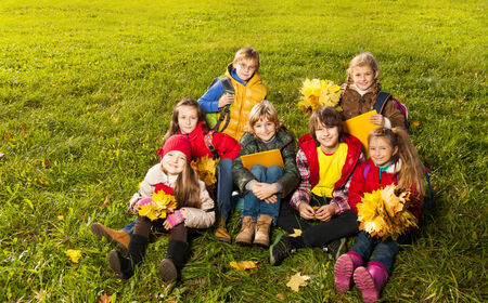 diversity children: Large group of kids sitting in the grass in autumn clothes with maple leaves bouquets and papers after school
