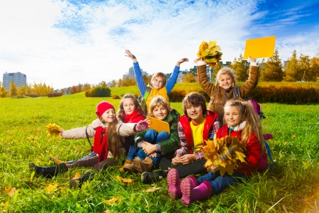 lifted hands: Large group of kids, boys and girls sitting in the grass in autumn clothes with maple leaves bouquets and papers after school with lifted hands Stock Photo