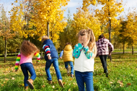 seek: Kids playing hide and seek in autumn park