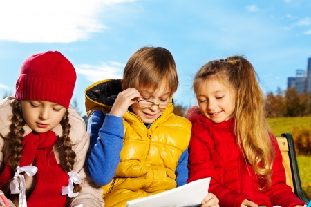 10 years old: Smart 10 years old boy in glasses read paper sitting on the bench with two girls friends