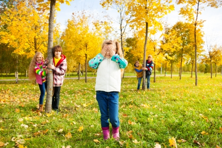 Kids play hide and seek with girl counting and friends hiding behind the trees photo