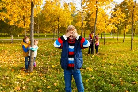 5 人の子供の遊び集団かくれんぼカウント少年と友達の木の後ろに隠れています。