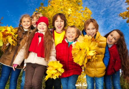 diversity children: Group of seven kids around 10 years old , boys and girls, standing together in the park with autumn yellow maple tree on background