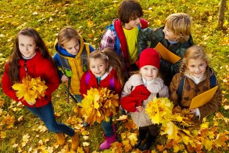 top 7: Grupo de los 7 ni�os de pie en el parque con las hojas de arce de color amarillo ramo en ropa casual oto�o, vista desde arriba