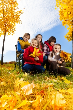 Five happy kids, boy and girls with maple leaves in the autumn park under the trees, low angle photo