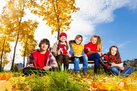 Four happy kids, boy and girls with maple leaves in the autumn park and sketching images photo