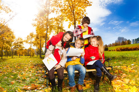 Group of five kids sitting together on the bench and drawing images and discussing  photo