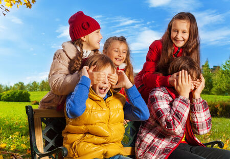 guess: Friends and surprise guess who action with girls hiding boys face with palms in autumn park Stock Photo