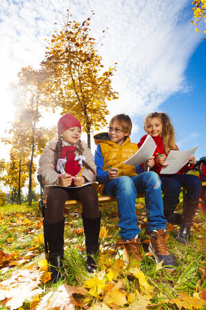 Group of three  kids, friends, boy and girls, sitting on the bench in autumn park on sunny day and draw pictures photo