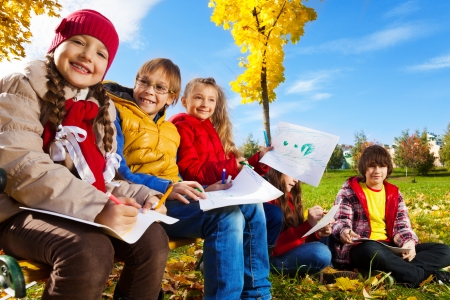 Group of smiling happy kids boys and girls sitting on the bench in the park under the autumn maple trees and drawing images photo