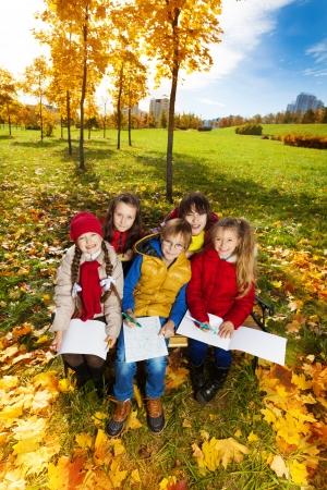 bocetos de personas: Grupo de amigos sonrientes felices los niños, muchachos y muchachas que se sientan en el banco en el parque bajo los árboles de arce del otoño y dibujar imágenes vista desde arriba