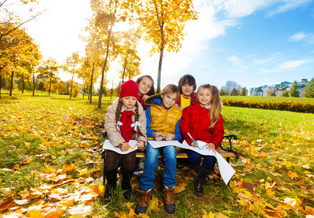 Group of smiling happy kids friends, boys and girls sitting on the bench in the park under the autumn maple trees and drawing images  photo