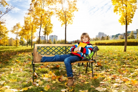 8 years: Happy boy sitting on the bench in the autumn park with a book Stock Photo