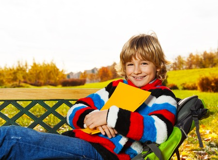 eight years old: Close portrait of happy boy sitting on the bench in the autumn park with a book Stock Photo