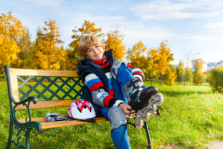 rollerblade: Happy blond boy putting on roller skates sitting on the bench in autumn park on sunny day