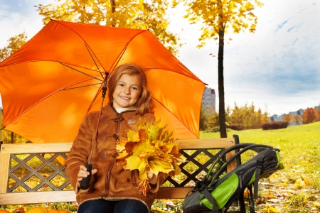 Beautiful girl sitting on the bench with bouquet of leaves and orange umbrella photo