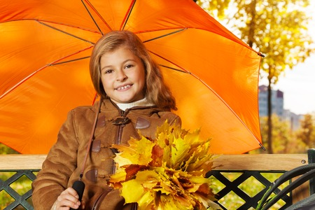 Close portrait of beautiful girl sitting on the bench with bouquet of leaves under orange umbrella  photo
