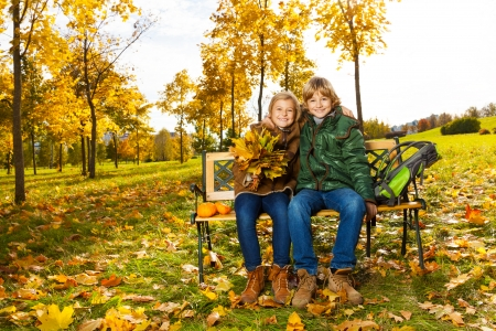 Portrait of two happy blond kids sitting on the bench in autumn park  photo