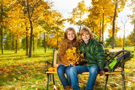 Couple happy blond kids sitting on the bench in the autumn park with bouquet of maple leaves photo